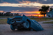 "Sunset over the 1962 Cadillac ""heel stone"" of Carhenge. Carhenge replicates England's Stonehenge using vintage American automobiles, near Alliance, Nebraska, in the High Plains region, USA. After studying Stonehenge in England, years later, Jim Reinders recreated the physical size and placement of Stonehenge's standing stones in summer 1987, helped by 35 family members. Reinders said, ""It took a lot of blood, sweat, and beers."" Carhenge was built as a memorial to Reinders' father. 39 automobiles were arranged in the same proportions as Stonehenge with the circle measuring a slightly smaller 96 feet (29m) in diameter. Some autos are held upright in pits five feet deep, trunk end down, while other cars are placed to form the arches and welded in place. All are covered with gray spray paint. Reinders donated Carhenge to the Friends of Carhenge, who gifted it to the Citizens of Alliance in 2013. Additional sculptures have been erected in the Car Art Reserve, where Reinders' ""Ford Seasons"" is made of four Fords, inspired by Vivaldi's Four Seasons. Also, 29-year-old Canadian Geoff Sandhurst sculpted a spawning salmon."