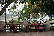 Elderly women sit and talk on a bench on the Strand overlooking the Hooghley River, Chandannagar, India