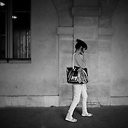 Paris - Place des Vosges - Juin 2012 - Une passante téléphone sous les arcades.
