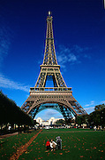 Eiffel Tower and park with blue sky and mother and child looking on from the lawn.