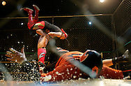 Halcon de Oro goes flying during a steel cage match as teammate Spawn lands hard in the forgeround.