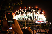 A supporter takes photos as fireworks light up the sky over the Olympic Stadium during the opening ceremony of the Tokyo 2020 Olympic Games, in Tokyo, on July 23, 2021. (Photo by Yuki IWAMURA / AFP)