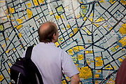 Tourist looks at a map of central London in Leicester Square, a hugely popular area for tourism in the West End, London.