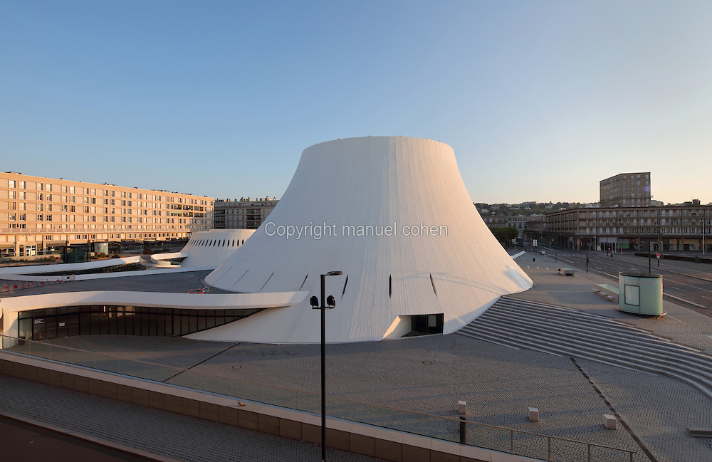 Le Volcan or the Volcano, auditorium opened 1982, designed by Oscar Niemeyer, 1907-2012, and Jean-Maur Lyonnet, at the Maison de la Culture du Havre, Le Havre, Normandy, France. Behind are apartment buildings designed by Auguste Perret, 1874-1954, who led the reconstruction of Le Havre in the 1950s, after the town was completely destroyed in WWII. The large volcano contains a 1200 seat theatre and 350 seat cinema, while the small volcano behind has a 500 seat hall and 80 seat auditorium and is now used as a reference library. The forum is built from concrete and the buildings are linked and accessed via ramps. The centre of Le Havre is listed as a UNESCO World Heritage Site. Picture by Manuel Cohen
