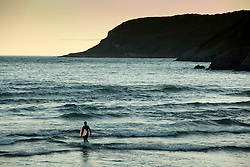 © Licensed to London News Pictures.23/07/2012. Caswell Bay, Gower Peninsula, Swansea, Wales, UK. As the sun sets at the end of the day, a lone surfer enters the water to catch the last waves of the day. Caswell Bay, on the Gower Peninsula. Photo credit : Dave Warren/LNP