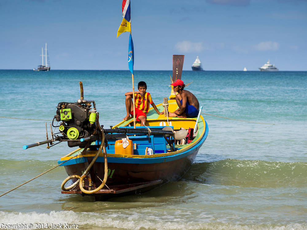 27 DECEMBER 2014 - PATONG, PHUKET, THAILAND:   Thai long tailed boat operators wait for tourists on Patong beach. Patong Beach is the largest beach on Phuket island. It's popular with tourists from Australia and Europe. In recent years it has become a leading destination for Russian tourists.  PHOTO BY JACK KURTZ