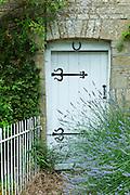 Lavender bush and traditional cottage entrance in the Cotswolds village of Bledington, Oxfordshire, UK