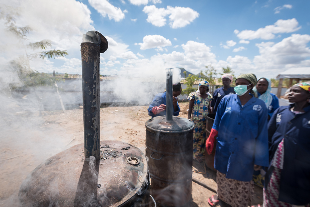 30 May 2019, Mokolo, Cameroon: Women oversee the metal containers in which biomass is burnt, in preparation to become charcoal. At the Minawao camp for Nigerian refugees, degradable and non-degradable waste are separated, so that biomass can be burnt in metal containers, processed and finally transformed into charcoal briquettes as a source of recycled energy to be used as firewood for cooking. With the support of an environment monitor  from the Lutheran World Federation World Service programme, the full process from waste to charcoal is managed and run by the refugees themselves. The Minawao camp for Nigerian refugees, located in the Far North region of Cameroon, hosts some 58,000 refugees from North East Nigeria. The refugees are supported by the Lutheran World Federation, together with a range of partners.