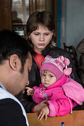 Jana, 23, and Tatiana, consults with Dr Mohsin Mehraj at an MSF mobile clinic held in the village of Gorodishe near Lugansk,