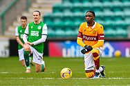 Devante Cole (#44) of Motherwell FC and the other players take a knee in recognition of the Black Lives Matter campaign, before the SPFL Premiership match between Hibernian FC and Motherwell FC at Easter Road, Edinburgh, Scotland on 27 February 2021.