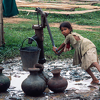 A homeless village girl from Bangladesh pumps water from the only well for hundreds of families living Mirpur Destitute Ramp near Dhaka in 1977.  Her mother had been left destitute, and widowed and homeless by a back to back cyclone and  brutal war of independence in 1971.