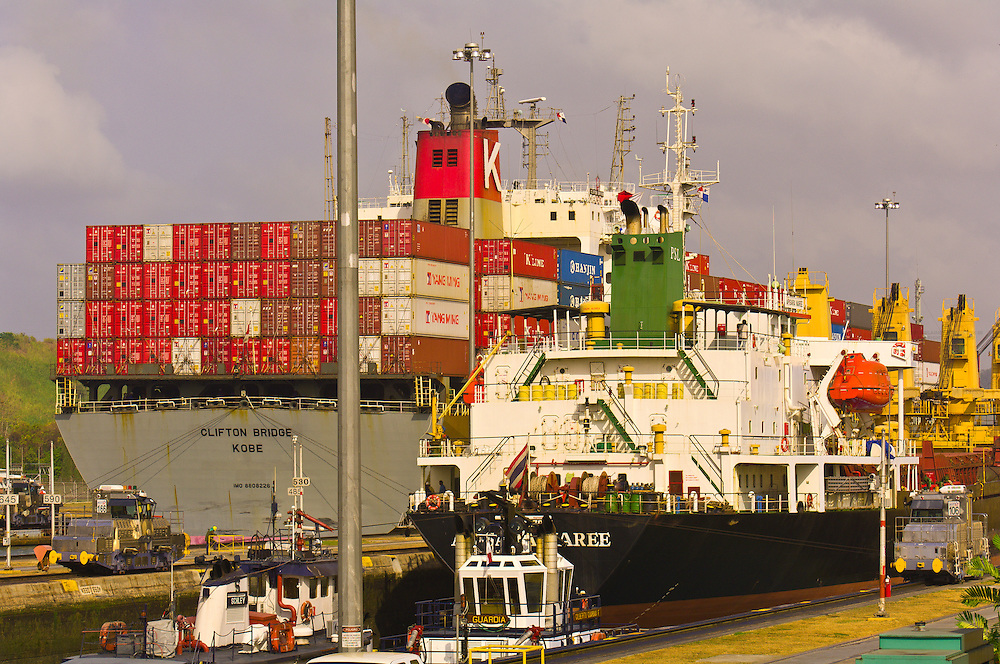 Tugboats escort a container ship passing through the Miraflores Locks on the Panama Canal, Panama
