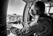 A door gunner observes a second Blackhawk helicopter on patrol in Iraq.