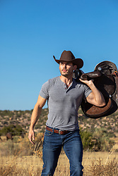 attractive cowboy with a saddle by a gate on a ranch