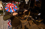 A teenage boy tries the sights of a WW2 sten gun during 1995 VE Day 50th anniversary celebrations in London. Picking up the replica weapon, the boy takes aim along the barrel of the gun, pretending to shoot an unseen enemy. Wearing military clothing and a hat with union jack colours plus flag in a back pocket, he plays the soldier at a time of remembrance of those killed during wartime. In the week near the anniversary date of May 8, 1945, when the World War II Allies formally accepted the unconditional surrender of the armed forces of Germany and peace was announced to tumultuous crowds across European cities, the British still go out of their way to honour those sacrificed and the realisation that peace was once again achieved. Street parties now – as they did in 1945 – played a large part in the country's patriotic well-being.