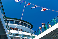 Looking up at the bridge of the Washington State ferry Wenatchee with tourists along the outside walkways enjoying summer weather with signal flags flying in support of Seattle's Seafair celebrations.