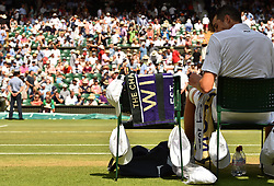 John Isner has multiple caps hanging on his chair during the men's semi final match on day eleven of the Wimbledon Championships at the All England Lawn Tennis and Croquet Club, Wimbledon.