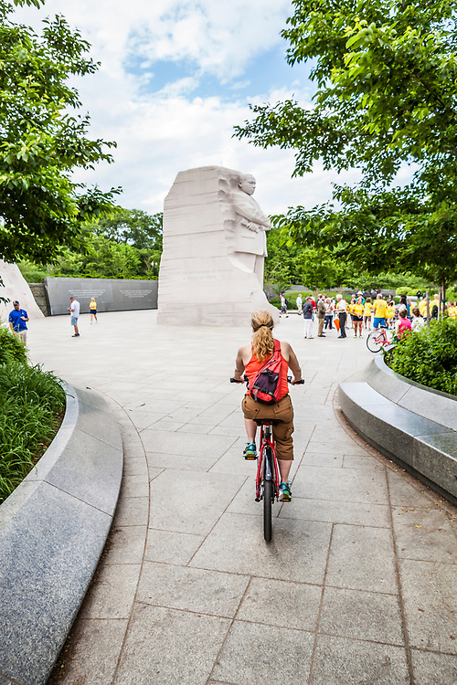 A woman approaches the Martin Luther King Jr memorial on a bike, Washington, D.C., USA.