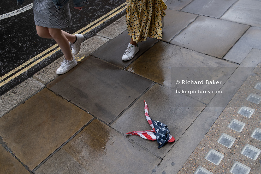 Pairs of legs walk past an American Stars and Stripes flag bandana lies on the wet pavement in the City of London, the UK capital's financial district, on 17th August 2020, in the City of London, England.