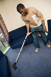 University student vacuuming the carpet in student accommodation,