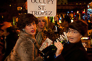 "Revelers drinking champagne with a sign ""Occupy St.Tropez"""