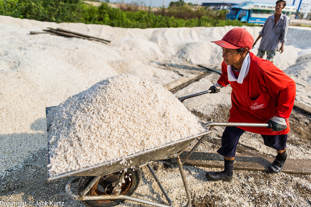 """28 MARCH 2014 - NA KHOK, SAMUT SAKHON, THAILAND: A worker stacks salt on a drying area in Samut Sakhon province. Thai salt farmers south of Bangkok are experiencing a better than usual year this year because of the drought gripping Thailand. Some salt farmers say they could get an extra month of salt collection out of their fields because it has rained so little through the current dry season. Salt is normally collected from late February through May. Fields are flooded with sea water and salt is collected as the water evaporates. Last year, the salt season was shortened by more than a month because of unseasonable rains. The Thai government has warned farmers and consumers that 2014 may be a record dry year because an expected """"El Nino"""" weather pattern will block rain in mainland Southeast Asia. Salt has traditionally been harvested in tidal basins along the coast southwest of Bangkok but industrial development in the area has reduced the amount of land available for commercial salt production and now salt is mainly harvested in a small parts of Samut Songkhram and Samut Sakhon provinces.    PHOTO BY JACK KURTZ"""