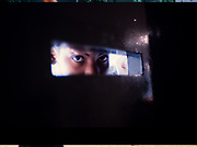 Atlanta Fulton County Juvenile Detention Center, Atlanta, GA. A juvenile male peers from a detention cell door at the