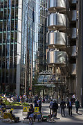 Londoners enjoy a warm afternoon beneath the tall architecture of the Lloyds Building right and other financial services offices in the City of London, the capitals historic financial district, on 2nd August 2018, in London, England.