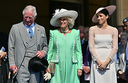 The Prince of Wales and the Duchess of Cornwall with the Duchess of Sussex (right) at a garden party at Buckingham Palace in London which she is attending as her first royal engagement after being married.