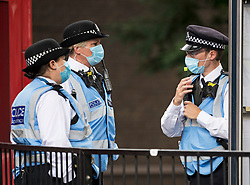© Licensed to London News Pictures. 30/08/2020. London, UK. Police officers wearing face masks patrol the streets of Notting Hill, West London, on the day of the 2020 Notting Hill Carnival, which is being held virtually this year due to COVID-19 restrictions. Members of the public have been warned against congregating in the Notting Hill Area to celebrate the event. Photo credit: Ben Cawthra/LNP