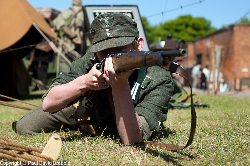 A world War two German Soldier wearing an M43 Ski Cap in the prone firing position using a Mauser K98 bolt action rifle May 2011 <br /> Image © Paul David Drabble