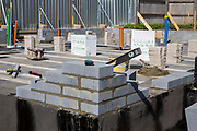 The freshly laid corner brickwork on the foundations of new house, part of a residential home construction site in Norwich. Norfolk.  United Kingdom