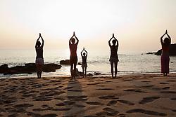Jul. 25, 2012 - Women practicing yoga on beach at sunset (Credit Image: © Image Source/ZUMAPRESS.com)