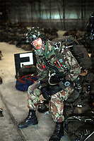 A soldier of the elite airborne Pathfinder force poses in his high altitude low opening (HALO) equipment before a jump, 1990. Photograph by Terry Fincher
