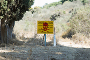 "Israel, Golan Heights, Military firing zone. A yellow and red warning sign ""Firing Area Entrance Forbidden"" in English, Hebrew and Arabic"