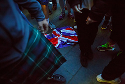 © Licensed to London News Pictures. 18/09/2014. Glasgow, UK. A damaged Union Jack flag is left on the ground after police officers separated Unionists and Scottish Independence campaigners who met at George Square in Glasgow whilst people of Scotland going to polling stations to vote on the Scottish independence referendum on Thursday, 18 September 2014. Photo credit : Tolga Akmen/LNP