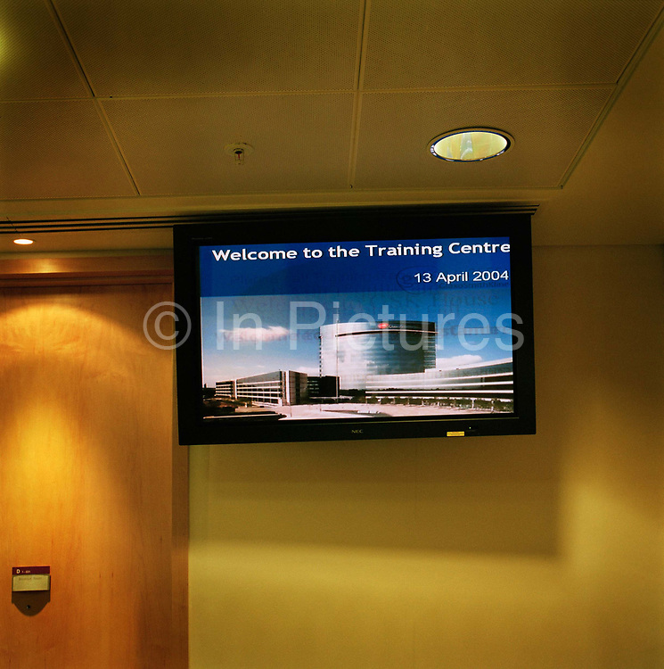 Interior shot of a screen  at a training centre in a London office conjures up visions of the nanny state and controlling organisations reminiscent of  George Orwell's big brother scenario in his classic novel 1984. From the series Desk Job, a project which explores globalisation through office life around the World.