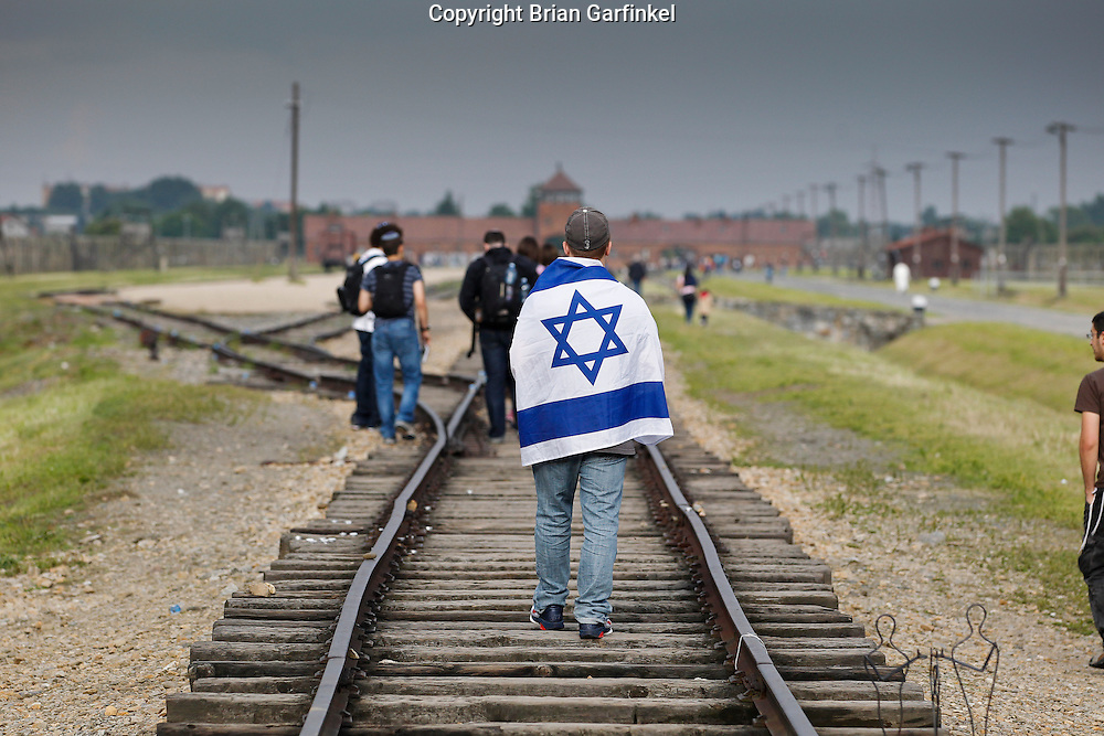 A young man wears an Israeli flag while walking on the train tracks towards the main gate from infside Auschwitz-Birkenau Concentration Camp in Poland on Tuesday July 5th 2011.  (Photo by Brian Garfinkel)