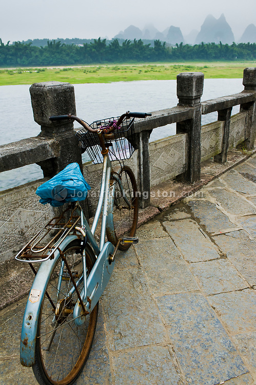 Blue bike leans against a concrete rail above the Lijiang River in Yangshuo, China.
