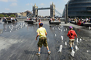 © Licensed to London News Pictures. 31/05/2013. London, UK Children play in the fountains with the Tower Bridge in the background. Children and office workers enjoy the hot weather near to City Hall and Tower Bridge in London today May 31st 2013. Photo credit : Stephen Simpson/LNP