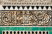 Detail of tile mosaics, stucco plasterwork and Islamic scripture on a wall inside the Bou Inania Medersa in Fes El-Bali, Morocco.