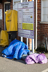 """A bundle of sleeping bags at the exit of River Street car park conceals a sleeping homeless person. After a public outcry against their """"homelessness support strategy"""" where rough sleepers would have been fined £100, Windsor council has shelved their plans. Windsor, Berkshire, February 16 2018."""