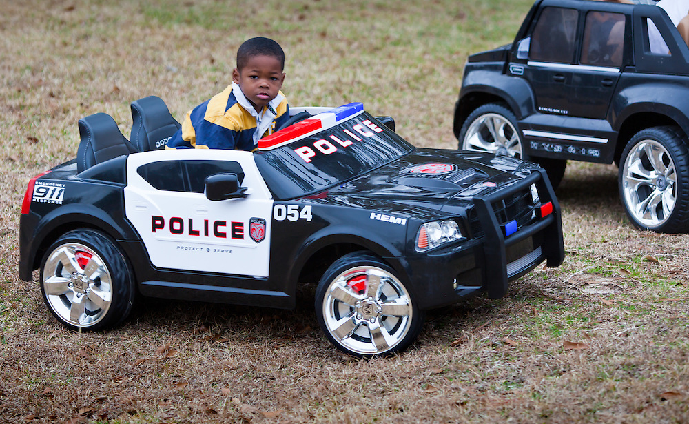 Little boy in Baton Rouge playing in a toy police car.