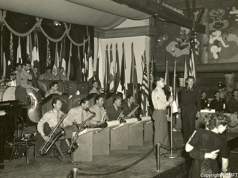11/22/45 The 684th Army Air Force Band plays for the audience during the Canteen's closing night. Corporal Bob Shaffer at the microphone. Earl R. Kinney is playing the baritone sax at the left.