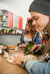 Young couple cutting vegetables in the kitchen, Munich, Bavaria, Germany