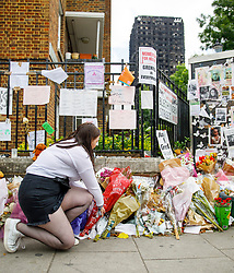 © Licensed to London News Pictures. 01/07/2017. London, UK. Lucy Ellis lays flowers for the victims of the Grenfell Tower fire on Saturday, 1 July 2017 on Latimore Road in west London. Photo credit: Tolga Akmen/LNP