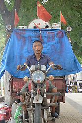 September 14, 2016 - Jinan, Jinan, China - Jinan, CHINA-September 11 2016:?(EDITORIAL?USE?ONLY.?CHINA?OUT) Jin Donghe rides his three-wheel motorbike in Jinan, capital of east China¬°¬Øs Shandong Province. Jin Donghe, a 36-year-old man, started his journey by the motorbike from Yanbian, northeast China¬°¬Øs Jilin Province, on May 18, 2016. He has traveled through about 3,400 kilometers by now, passing north China¬°¬Øs Liaoning, Tianjin, Beijing and Hebei. Jin spent no more than 2,000 yuan (about US$ 300) refitting the motorbike, equipping it with solar power equipment, television and sound box. He plans to travel around the country in three and a half years by motorbike. (Credit Image: © SIPA Asia via ZUMA Wire)