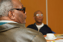 Person with visual impairment in discussion group at at a resource for people with physical and sensory impairment.