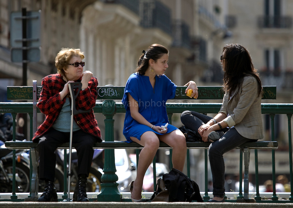 By the Canal St. Martin. Older woman with crutch sitting on bench beside the canal while two girls talk. Can't help thinking she's lonely, and wants to join in. Of course, I could be wrong.