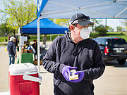 09 MAY 2020 - DES MOINES, IOWA: An artisan cheese maker gets cheese for a customer at a drive through farmers' market in Des Moines. The Governor allowed farmers' markets across the state to reopen last weekend, but limited them to selling just food stuffs. They are not allowed to have entertainment or sell non-food items. Most farmers' markets in Iowa are taking a wait and see approach to reopening. The Downtown Farmers Market in Des Moines announced they won't reopen until July. Three vendors set up their own drive through farmers' market in the parking lot of Des Moines theatre Saturday. Hundreds of people got in line to buy fresh produce and artisan cheese. More than 11,670 people have tested positive for COVID-19 in Iowa and more than 250 have died from the disease.        PHOTO BY JACK KURTZ